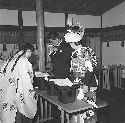 The miko (shrine maiden) offers sacred sake to...