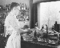Technician standing at laboratory table,...