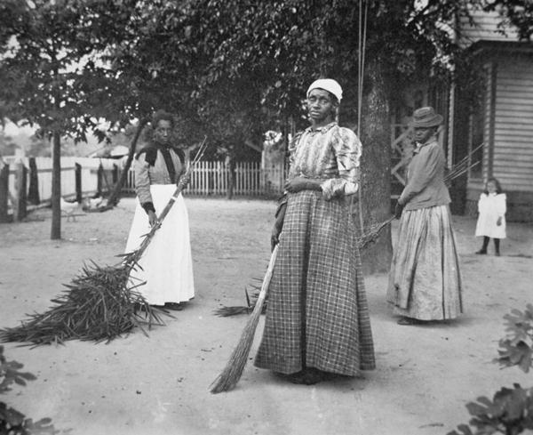 black & white photo of female servants using brooms