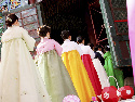 Women enter a temple in a traditional Buddhist...