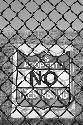 A no trespassing sign hangs on a portion of fence...
