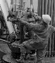 Photograph shows two men operating oil equipment...