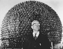 Buckminster Fuller, stands before a geodesic dome...