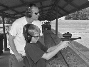 A father teaches his son how to aim and fire a...