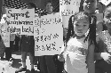 Rin, 4, daughter of a garment worker, stands...