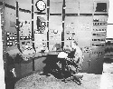 Enrico Fermi seated at the control panel of a...