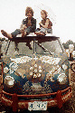 Concertgoers on the roof of a Volkswagen bus at...