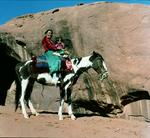 Navajo mother and child on horseback at Navajo Reservation, Monument Valley, Arizona (photo)