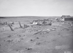 Car and farm machinery buried by dust and sand, Dallas, South Dakota, 1936 (b/w photo)