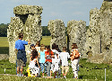 Visitors at Stonehenge standing behind fencing,...