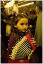 A Roma child plays accordian with her father on...