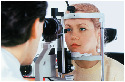 Optometrist administering glaucoma test to female...