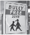 A Bully-Free Zone sign hangs in a school in...