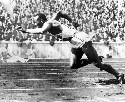 Jesse Owens participating in the 1936 Olympic...