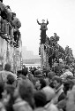 Berliners celebrate on top of the wall as East...