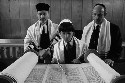 A boy recites from the Torah during his bar...