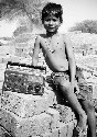 A young Indian boy with his father's radio. In...