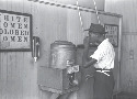 "Man drinking at ""Colored"" water cooler in..."
