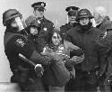 A protestor is carried off by police at a...