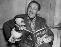 Walt Disney poses with a toy Donald Duck while...