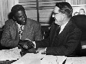 Jackie Robinson shakes hands with Branch Rickey...