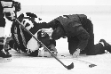 An injured hockey player is attended to on the...
