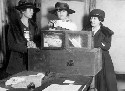 Three suffragists casting votes in New York City,...