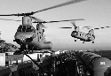 Sea Knight helicopters maneuver the flight deck...