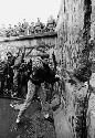 A demonstrator from West Berlin tearing away part...