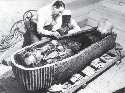 Archaeologist Howard Carter examines the...