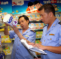 Chinese food inspectors examine milk powder at a...